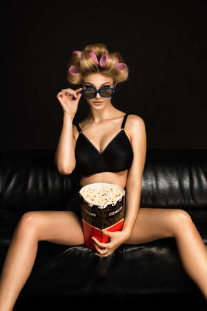 Sexy pinup Girl eating popcorn with scared expression.