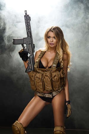 Young beautiful sexy blond Woman holding Handgun