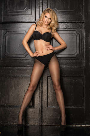 Young sexy blonde woman in dark lingerie and tight