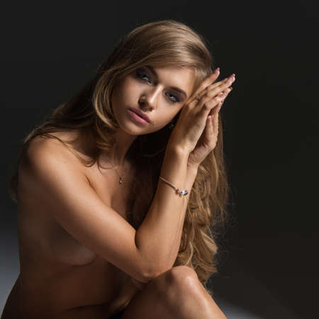 beautiful naked woman: Beautiful young naked blonde woman sitting over the background Stock Photo