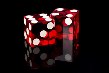 Two red dices on a black background 스톡 콘텐츠