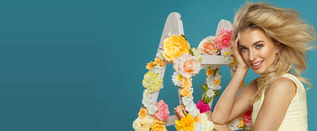 articles: Delicate blonde woman with floral white lAdder Stock Photo