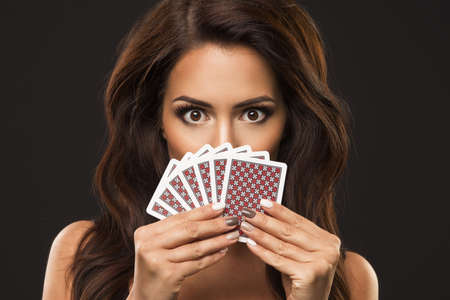 Beauty woman is hiding under playing cards, only eyes and poker face Imagens