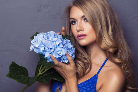 Sensual beautiful blonde woman posing with flower. photo