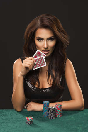 Sexy brunette woman with poker cards on black background