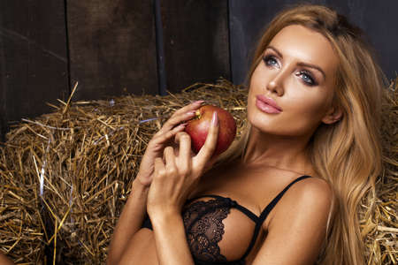 salud sexual: Sexy beautiful girl sitting on a floor with apple in the hand.
