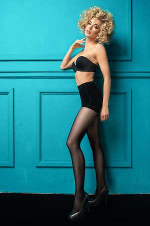 Sexy blonde Mädchen in Strumpfhosen über Türkis Hintergrund