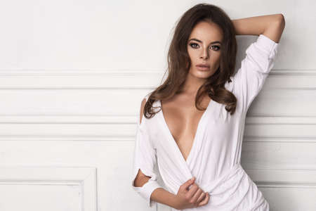 Young sexy brunette woman in white room Stock Photo