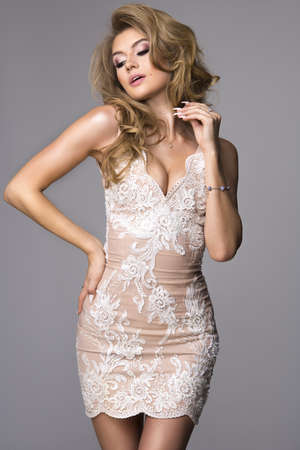 Sensual beautiful blonde woman posing in shining dress. Girl with long curly hair. Stock Photo