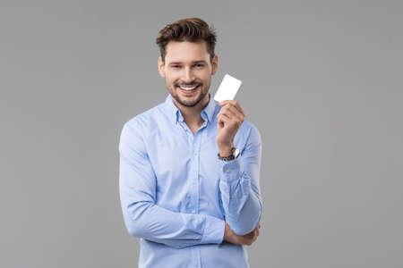白いカードと青いシャツのハンサムな男