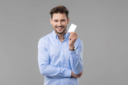 Handsome man in blue shirt  with white card Stock Photo