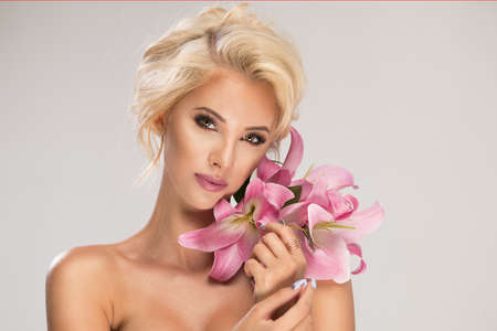 Beautiful blonde smiling woman with a lily Standard-Bild - 108857615