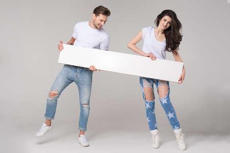 Happy summer couple with white board Standard-Bild - 108857616