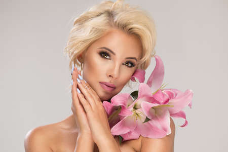 Beautiful blonde smiling woman with a lily Standard-Bild - 108857687