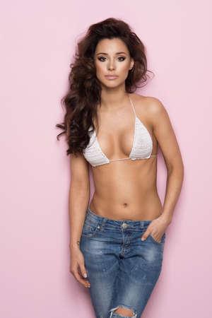 Sexy brunette woman wear pastel swimwear over pink background Standard-Bild - 108857714