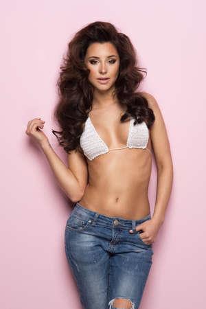 Sexy brunette woman wear pastel swimwear over pink background Standard-Bild - 108857749