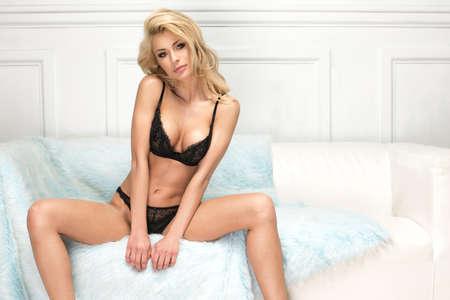 Sexy blonde woman in black lingerie in white room Standard-Bild - 110292503