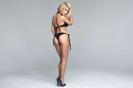 Sexy blonde woman in black swimwear over grey background Standard-Bild - 110292504