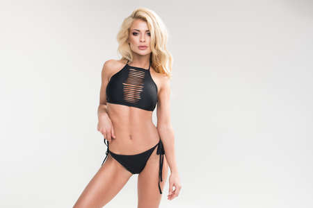 Sexy blonde woman in black swimwear over grey background Standard-Bild - 110292505