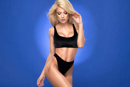 Sexy blonde woman inblack swimwear over blue background Standard-Bild - 110915881