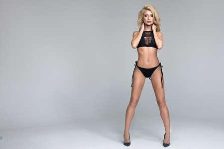 Sexy blonde woman in black swimwear over grey background Standard-Bild - 109613070