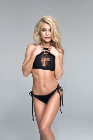 Sexy blonde woman in black swimwear over grey background Standard-Bild - 109613072