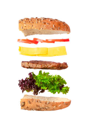 Delicious tasty hamburger with flying ingredients isolated on white background. Burger parts flying in air. Floating Burger Stok Fotoğraf