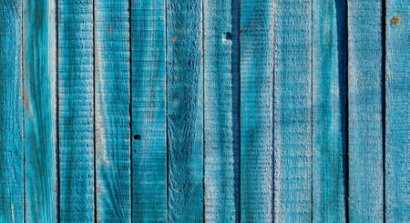 Texture of old blue wooden fence. Rustic wooden boards for background.
