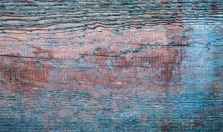 The texture of old board with peeling blue paint.