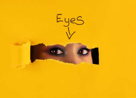 Beautiful face of a girl with colorful make-up looks through the torn hole in yellow paper. Stockfoto