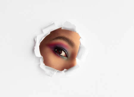 Beautiful girl with colorful makeup looking through a round torn hole in white paper background.