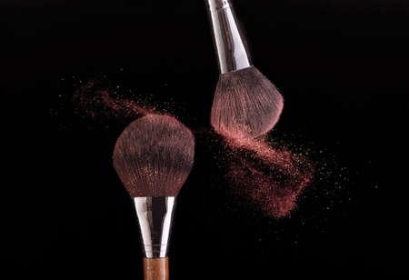 Due spazzole che spruzzano polvere su sfondo nero.