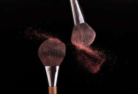 Two brushes spraying powder on a black background.