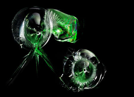 Bullet holes with green reflections in glass on black background. Macro. Side view. 版權商用圖片