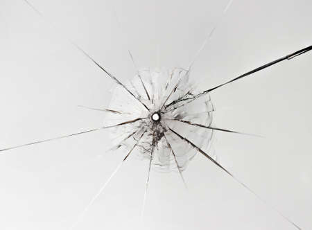 Small hole in glass with long cracks on white background. Close up.