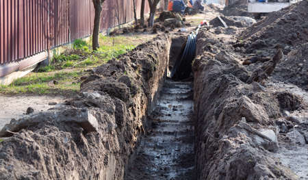 Earthwork. A deep long trench dug in the ground for laying cables, pipes. Telecommunications industry. Stockfoto