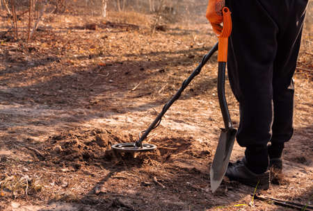 Man with a metal detector and a shovel is looking for a treasure in the forest. Banque d'images