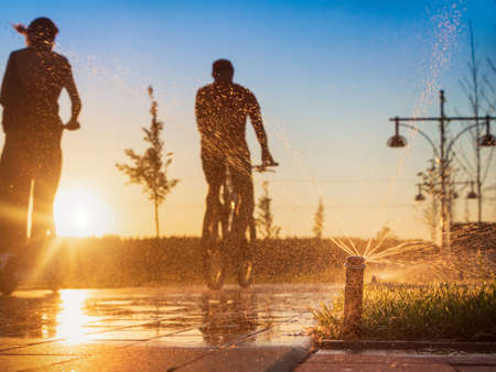 Automatic sprinkler system watering the lawn on a background of man on bike and girl on scooter riding in public park at sunset.