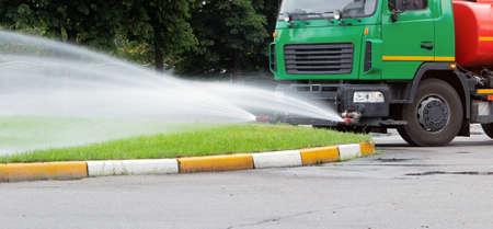 A truck for watering the lawn pours water on the lawn with water jets. City lawn care services. 스톡 콘텐츠