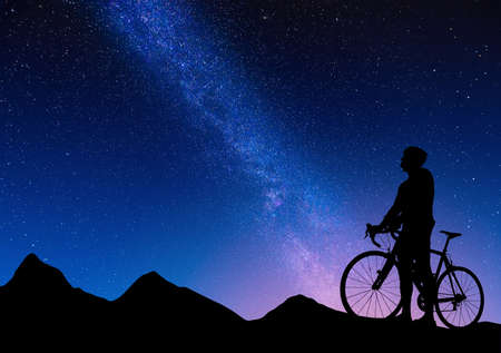 Silhouette of cyclist on a road bike against the background of the milky way. Beautiful night landscape of a road cyclist in the mountains on the starry sky background. Sports lifestyle.