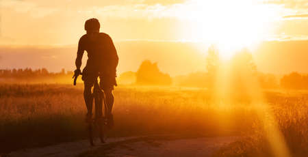 Silhouette of a cyclist riding a trail in a field on a dramatic sunset background.
