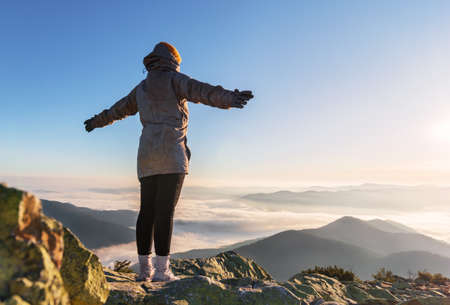 Young happy woman with raised hands on a mountain peak in low clouds looking at beautiful view at sunrise. Success and victory concept.