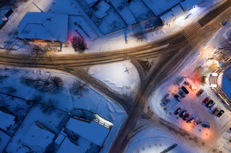 Traffic junction in a snowy night city from aerial top view.