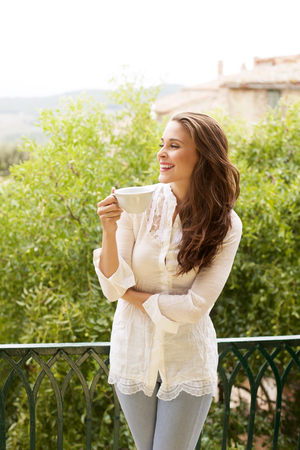 happy young woman: Portrait of happy young woman with cup of hot beverage