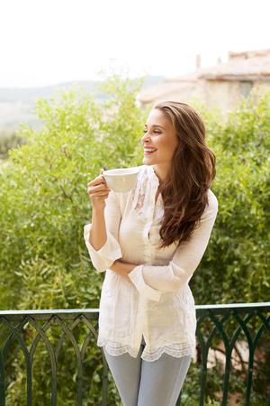 mujeres fashion: Retrato de mujer joven feliz con la taza de bebida caliente
