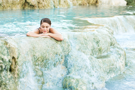 aqua park: Young woman lying in the natural pool, Saturnia, Italy