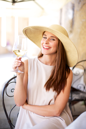 Young happy woman with glass of white wine Stockfoto