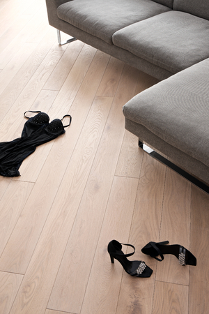 Women shoes and clothes lying in the front of a sofa Stock Photo