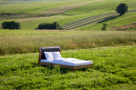early morning: Bed in a grass field- concept of good sleep Stock Photo