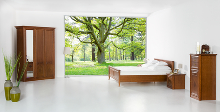 Bed in the room opened on the forest - concept of good sleep
